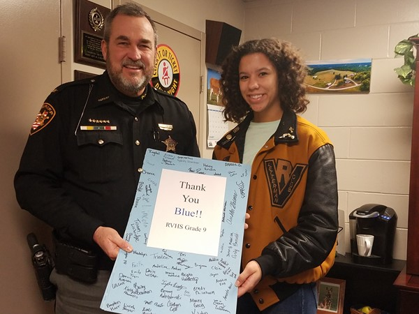 Skyler Stewart presenting Sheriff Rogers thank you cards from RVHS students for Law Enforcement Appreciation Day